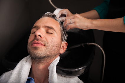 Relaxed young man getting his hair washed before getting a haircut at a salon